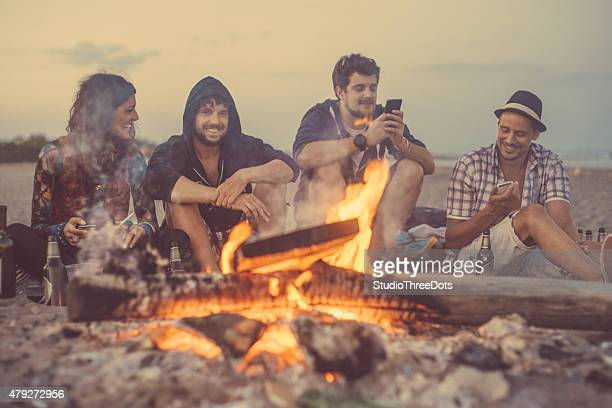 friends sitting around a camp fire