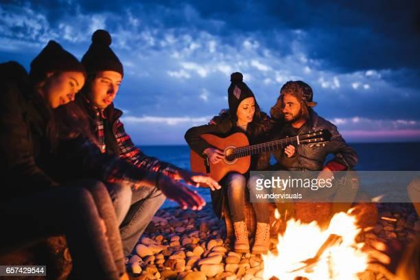 Freunde sitzen um ein Lagerfeuer am Strand, Gitarre spielen
