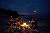 Friends sitting around campfire on beach at night