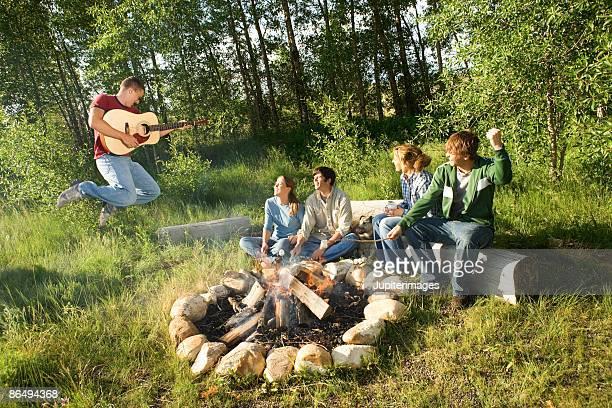 Friends sitting around campfire watching friend play guitar