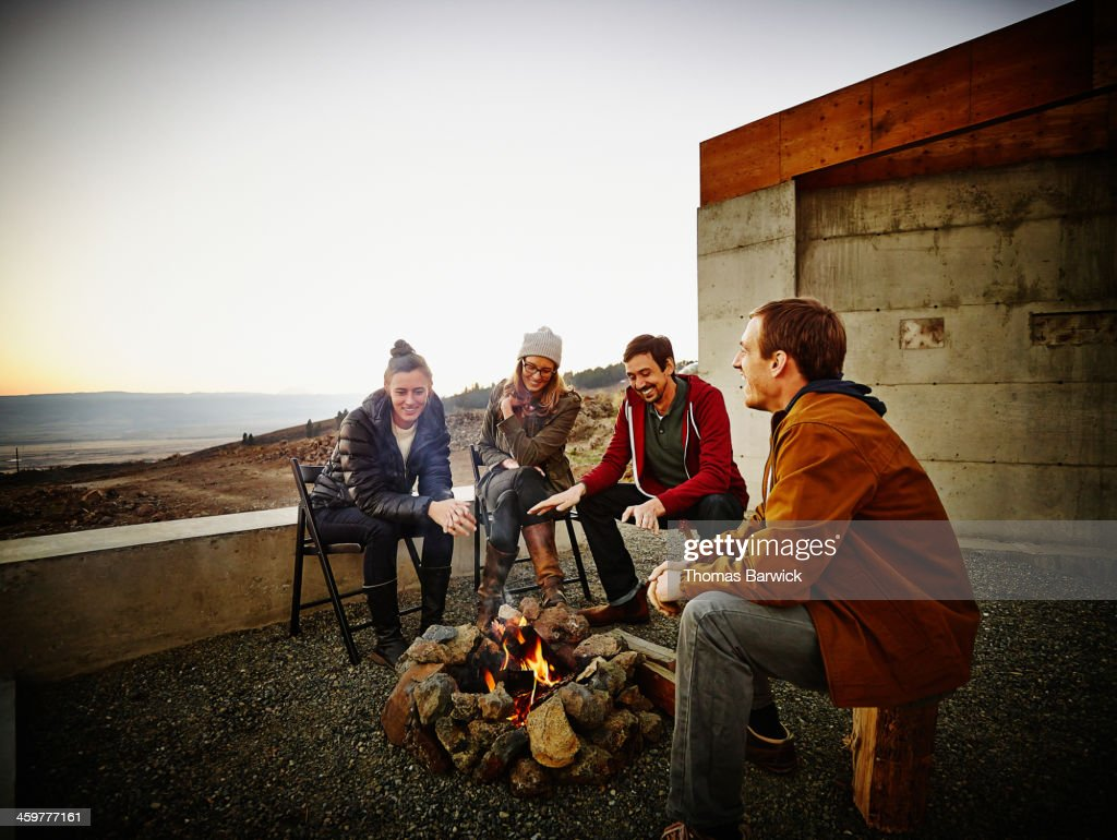Friends sitting around fire pit at sunset : Stock Photo