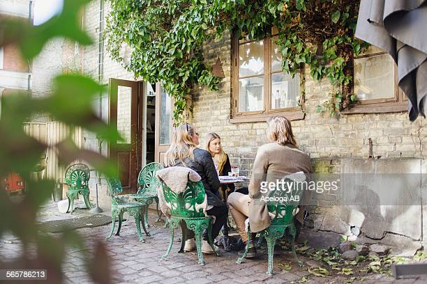 Friends sitting at outdoor restaurant