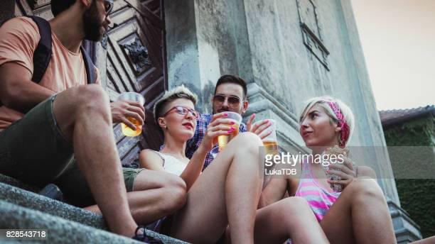 Amis, assis à l'escalier et boire de la bière