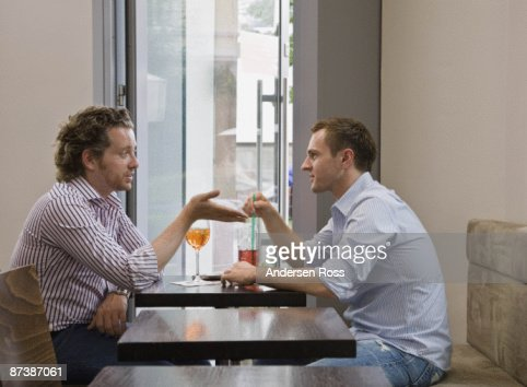 Friends sitting at table talking : Stock Photo