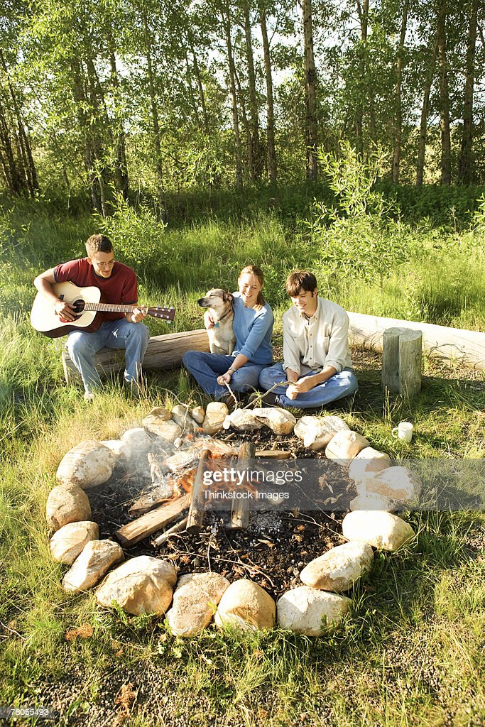 Friends sitting by campfire : Stock Photo