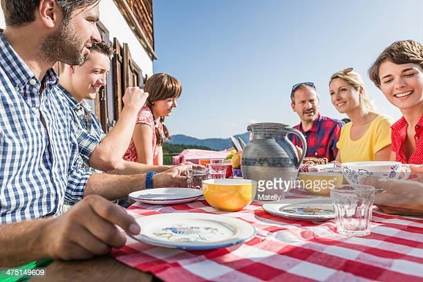 Friends sitting for breakfast outside chalet, Tyrol, Austria