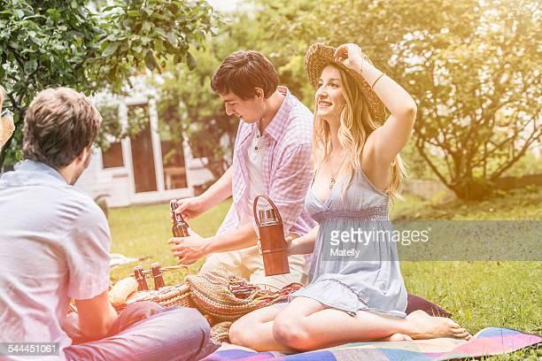 Friends sitting having picnic in garden