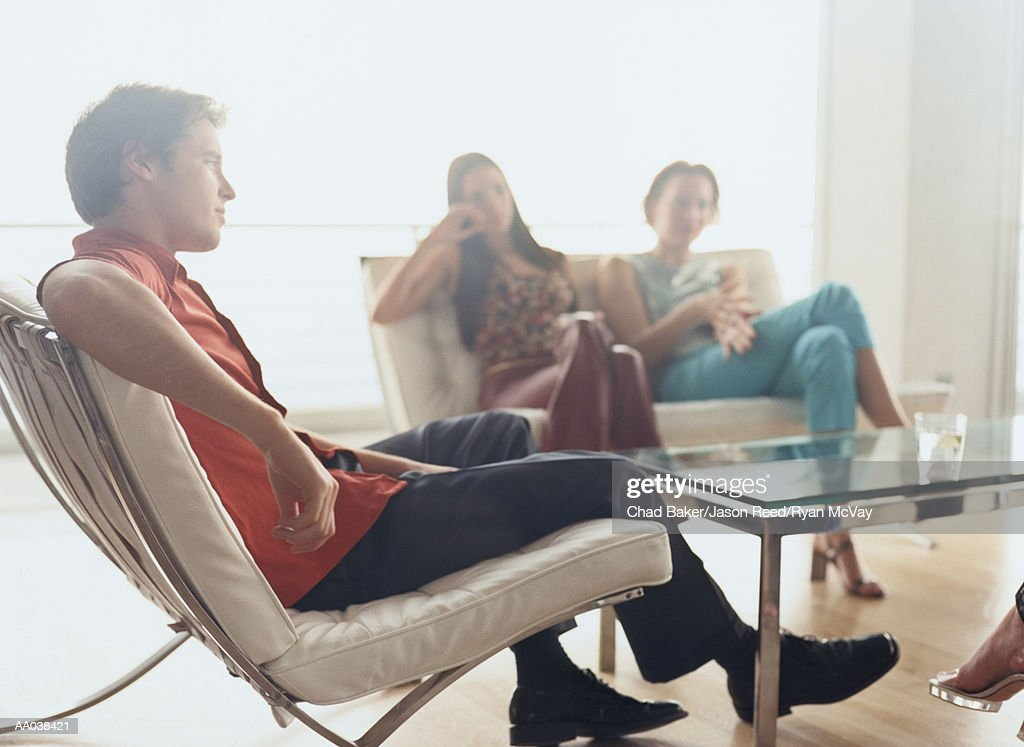 Friends Sitting in a Living Room : Stock Photo