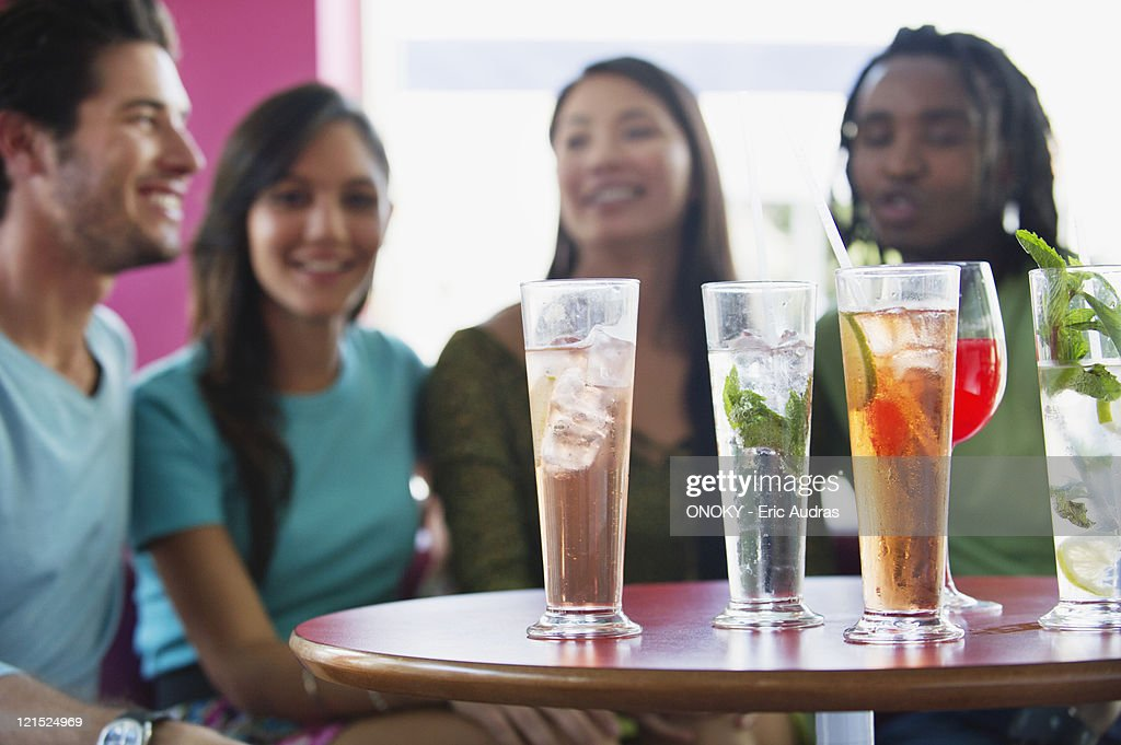 Friends sitting in a restaurant with focus on beverage : Stock Photo