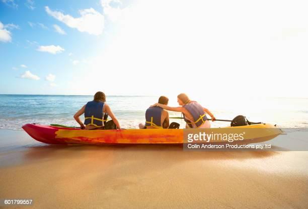 Friends sitting in canoe on beach
