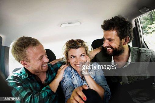 Friends sitting in car, having fun