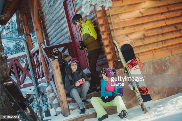 Friends sitting in front of cottage on snowy mountain