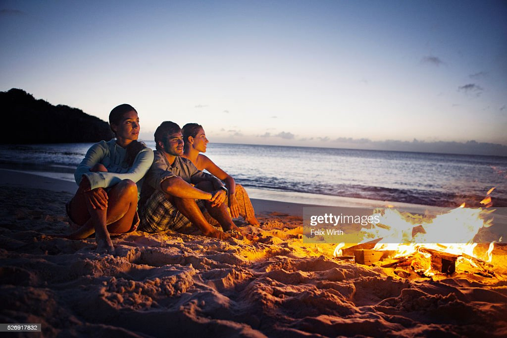 Friends sitting on beach at campfire : Stock-Foto