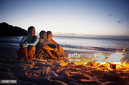 Friends sitting on beach at campfire : Stock Photo