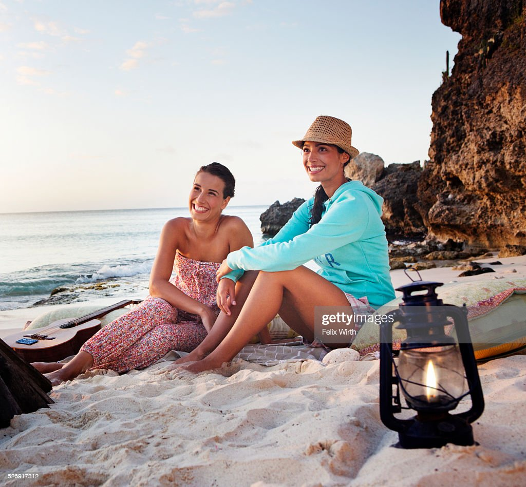 Friends sitting on beach at dusk : Stock Photo