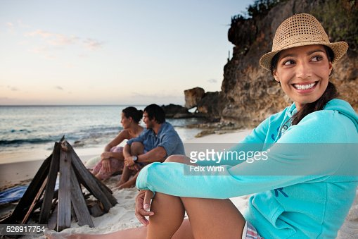 Friends sitting on beach at dusk : Foto de stock