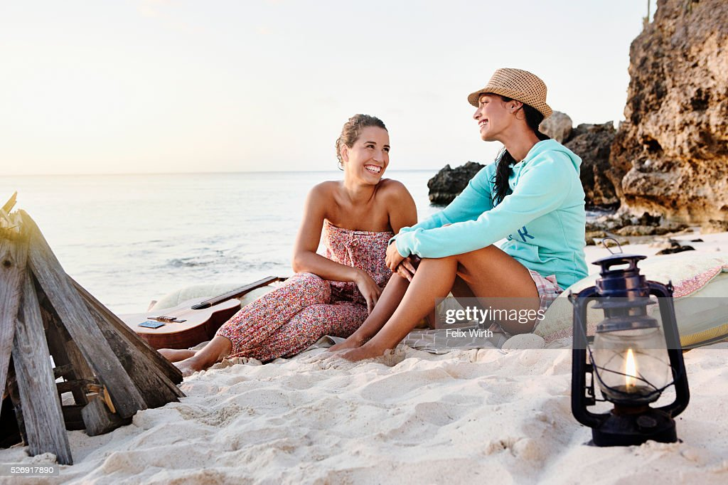 Friends sitting on beach at dusk : Bildbanksbilder
