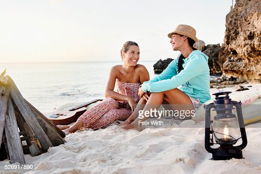 Friends sitting on beach at dusk : Photo