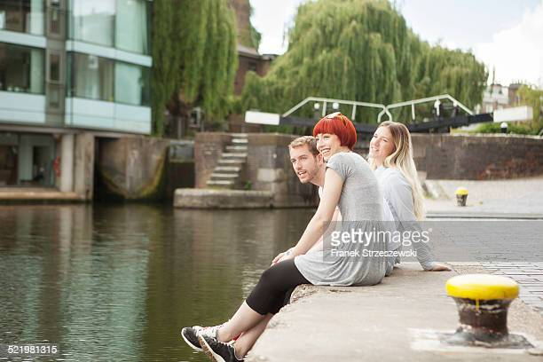 Friends sitting on canal side, East London, UK