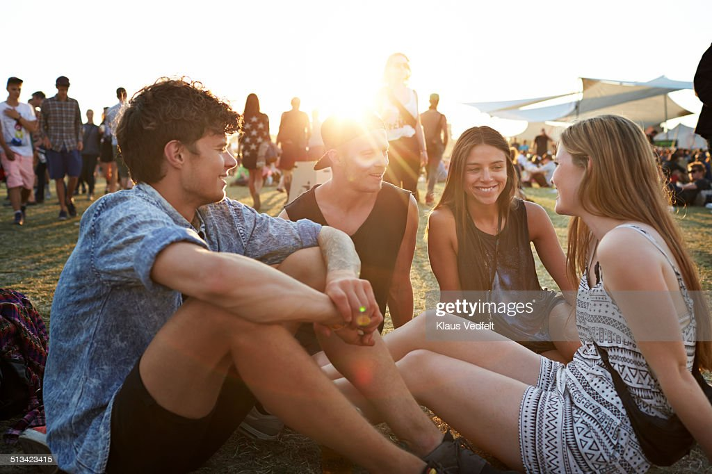 Friends sitting on grass at sunset : Stock Photo