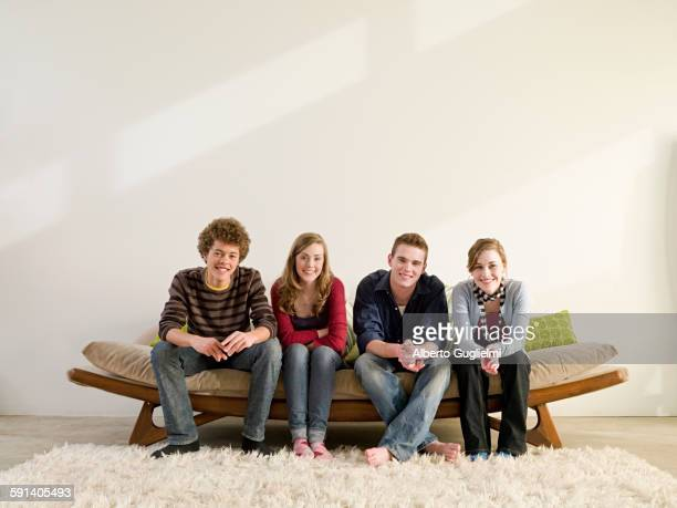 Friends sitting on modern sofa in living room