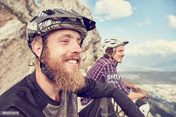 Friends sitting on mountain peak looking at view smiling, Innsbruck, Tyrol, Austria