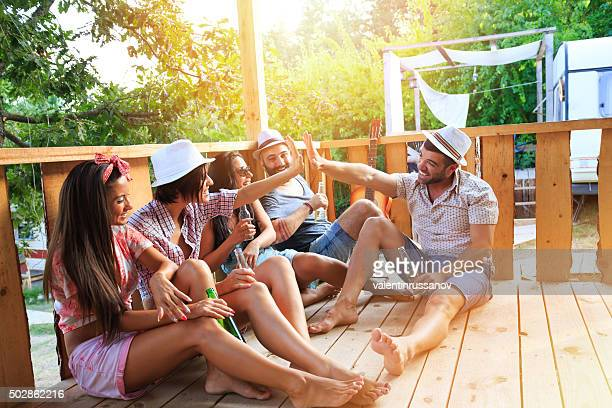 Friends sitting on pavilion in front of caravan