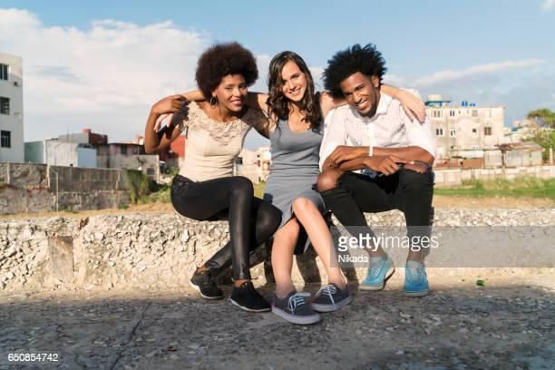 friends sitting on retaining wall at public park, Havana, Cuba