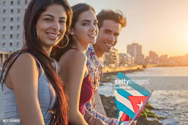 Freunde sitzen auf Stützmauer auf dem Seeweg in Havanna