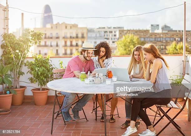 Friends sitting on rooftop terrace, Barcelona
