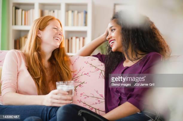Friends sitting on sofa talking