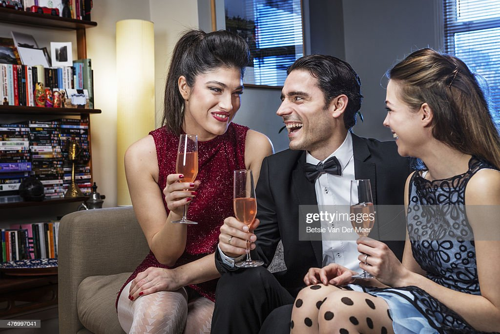 Friends sitting on sofa,with champagne, laughing. : Stock Photo