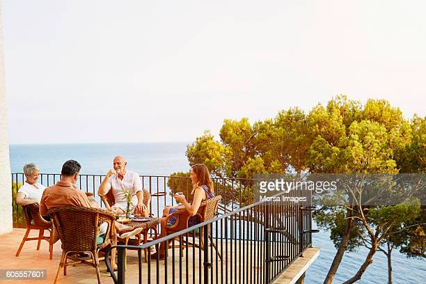 Friends sitting on terrace surrounded by ocean