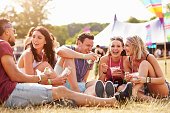 Friends sitting on the grass eating at a music festival