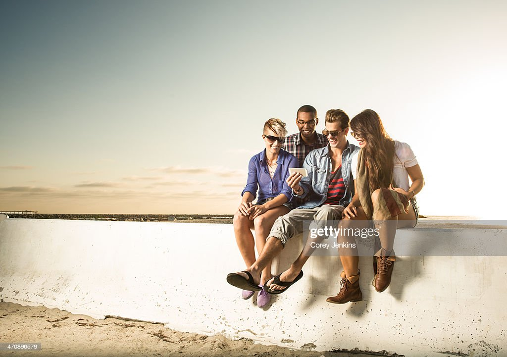 Friends sitting on wall with smartphone, Mission Beach, San Diego, California, USA : Stock Photo