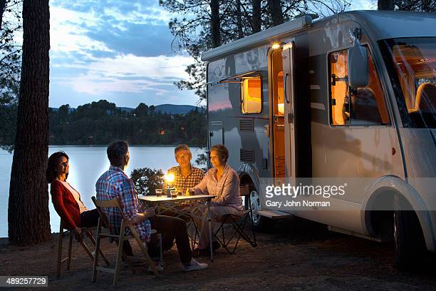 Friends sitting outside motorhome in the evening