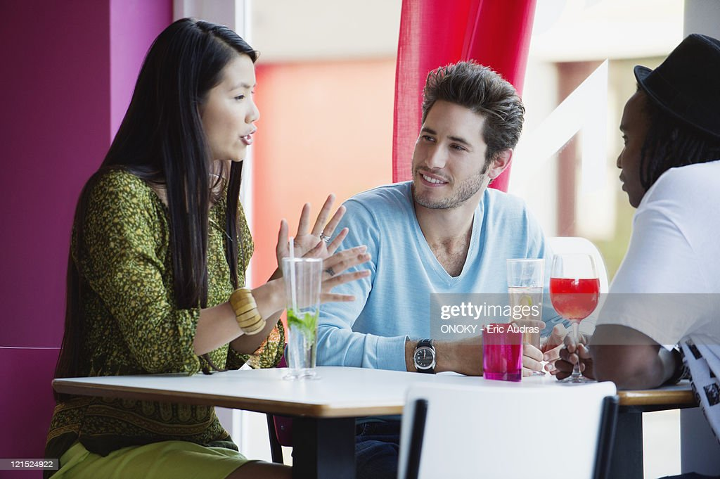 Friends sitting together and talking in a restaurant : Stock Photo