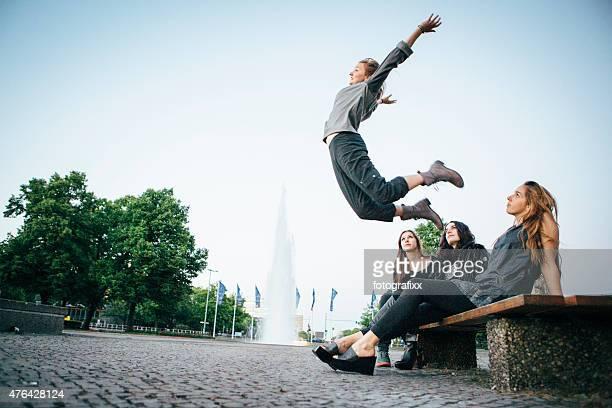 Freunde sitzen zusammen und achten Sie auf eine jumping Frau