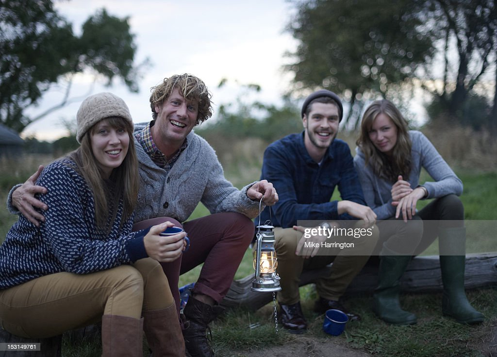 Friends sitting together outside in early evening. : Stock Photo