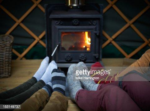 Friends sitting with feet around log fire in yurt.