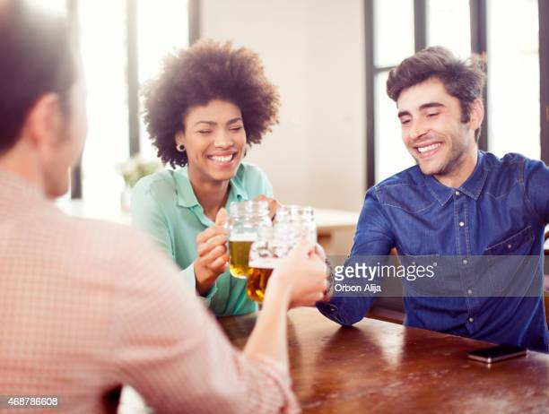 Friends smiling and drinking at restaurant