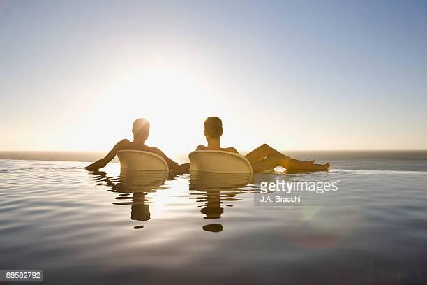 Friends soaking in infinity pool near ocean
