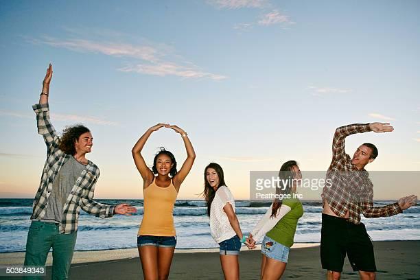 Friends spelling Love on beach