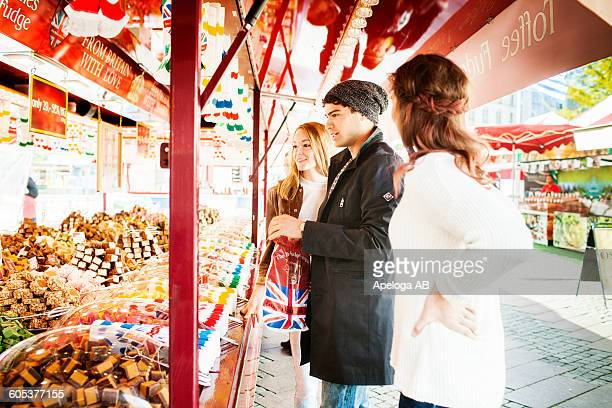 Friends standing and buying fudge from stall in market