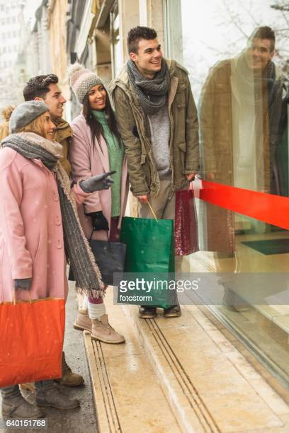 Friends standing in front of store window
