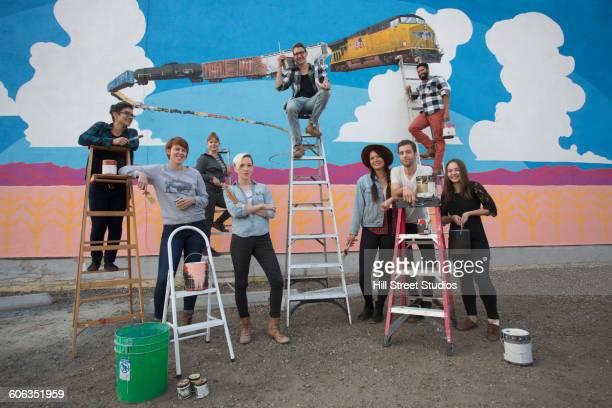 Friends standing near mural wall