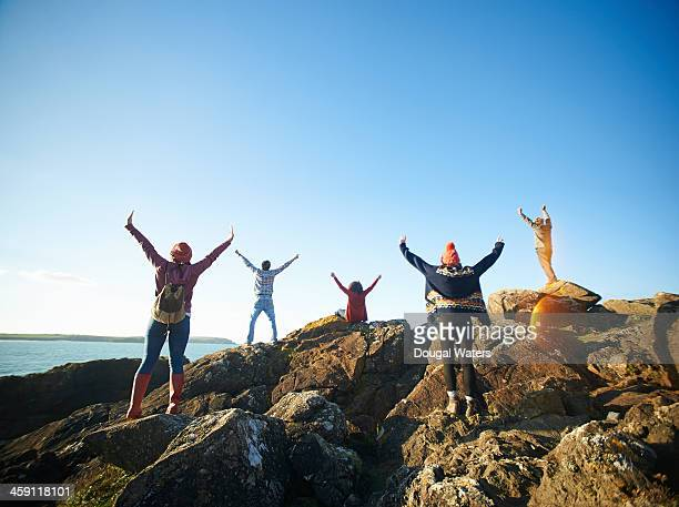 Friends standing on coastal rocks with arms raised