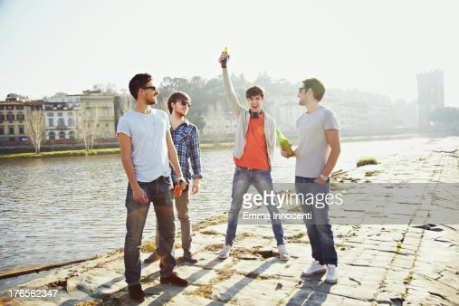 Friends standing on river bank with beer