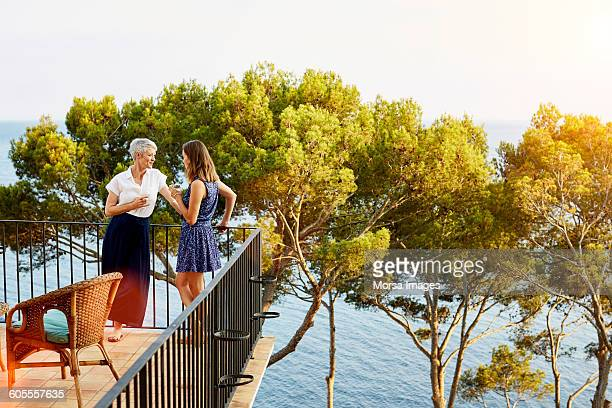 Friends standing on terrace by trees and ocean