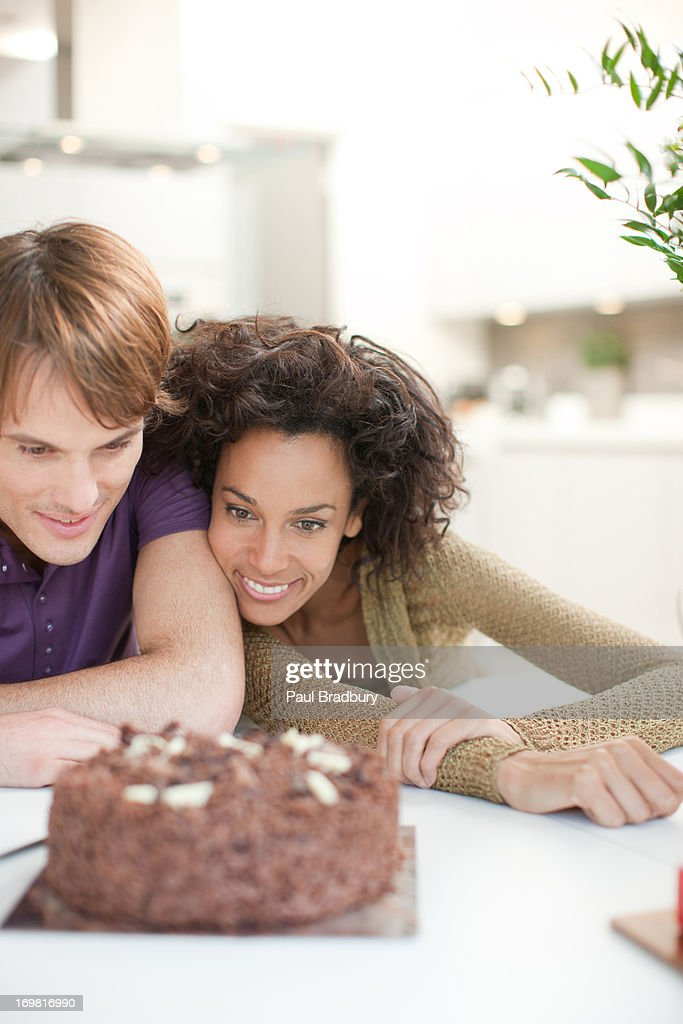 Friends staring at chocolate cake : Stock Photo